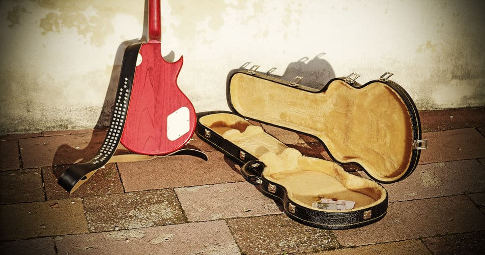 38151529 - guitar case with coins and bills in vintage tone